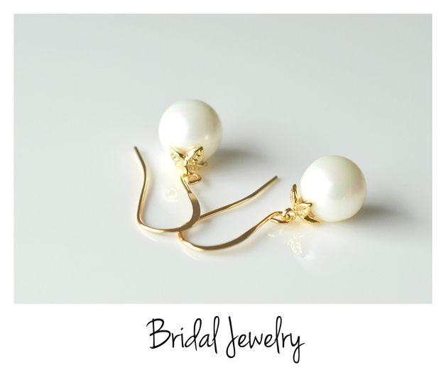 An dem schlichten vergoldeten Ohrhaken hängt eine runde Muschelkernperle (ca. 10mm) in weiß. Die sprichwörtliche Krönung sitzt auf der Perle in Form zarter Blütenblätter.  +Sag ja mit...