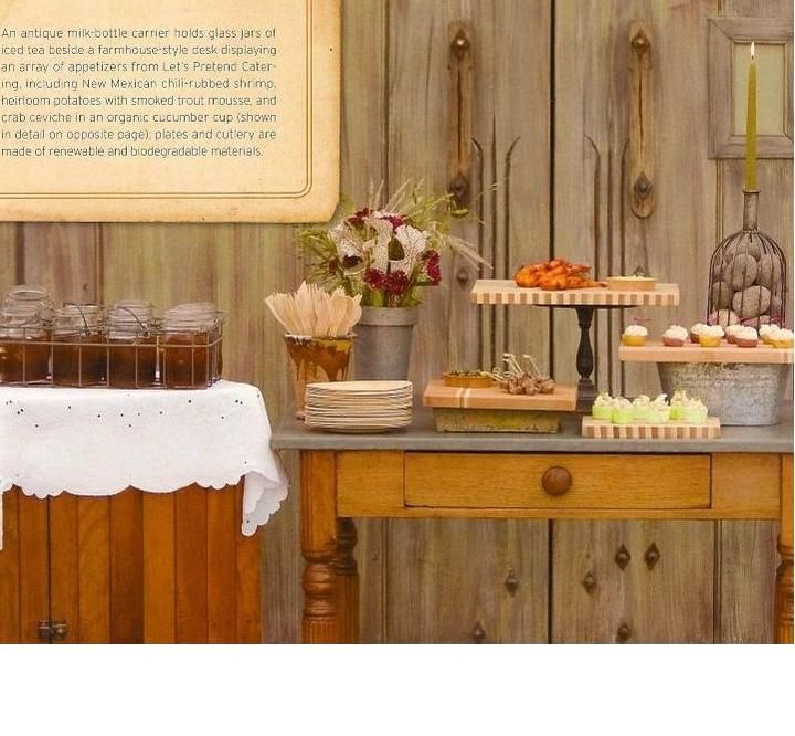 An antique milk-bottle carrier holds glass jars of iced tea beside a farmhouse-style desk displaying an array of appetizers.  Cutting boards paired with a variety of everyday objects are used as risers.