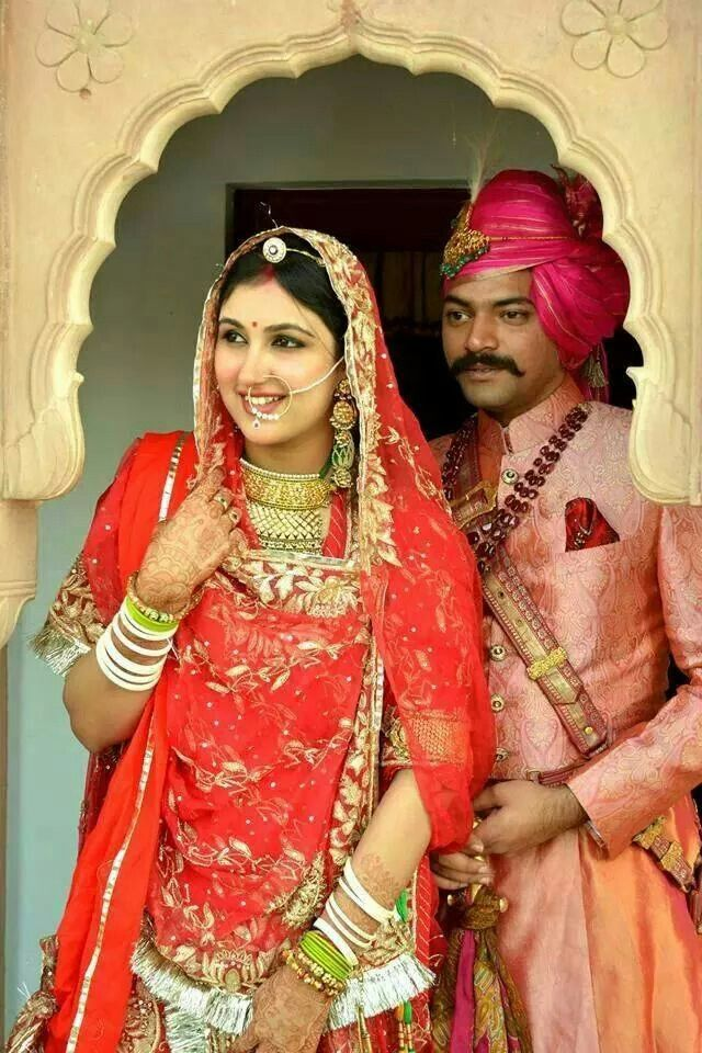 Rajasthani bride and groom. Indian bride wearing bridal lehenga and jewelry.