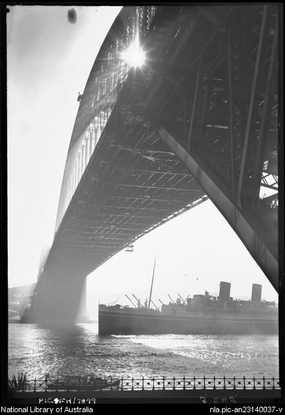 Effect shot of Sydney Harbour Bridge from Dawes Street with R.M.S. 'Mooltan' passing underneath [Sydney] between 1910 and 1962. by Frank Hurley, Australian photographer