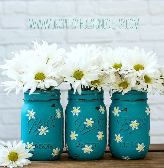 Set of three pint-sized mason jars hand painted and distressed in teal with white and yellow daisies. Perfect gift idea for Mothers Day