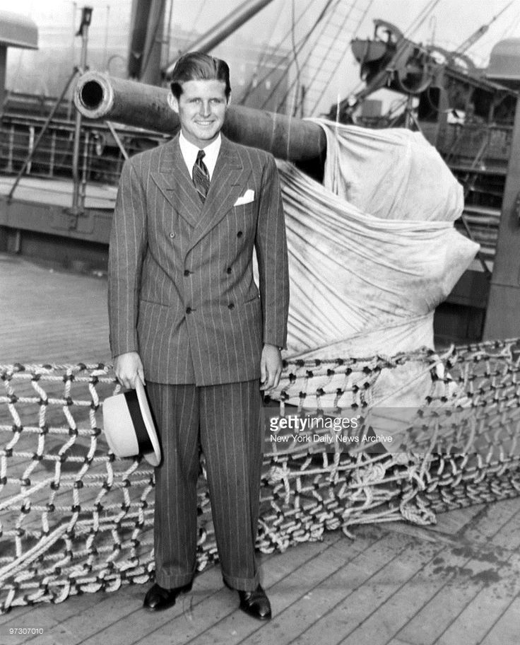John F. Kennedy, [sic]son of the U.S. Ambassador to Great Britain, arriving in New York aboard the SS Mauretania. He stands next to an anti-aircraft gun on board the ship., photo shows Joseph Kennedy Jr.
