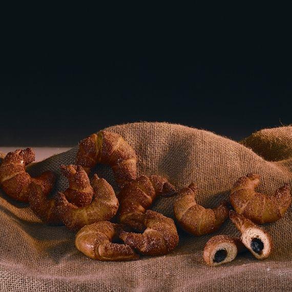 Rogaliki z powidłami Przygotowane z ciasta półfrancuskiego, nadziewane powidłami śliwkowymi lub nadzieniem różanym, dekorowane cukrem złocistym.