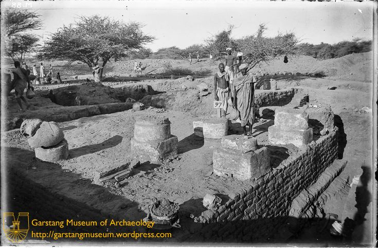 "JG-M-AA-054 (1912) - The excavations at Meroë revealed a large number of monumental buildings at the site, most of which were identified as temples or palaces. Here, a small columned enclosure, built as part of one of the temples at Meroë, is seen. Garstang referred to this as the ""prostyle temple"". A workman holds the site number for the building."