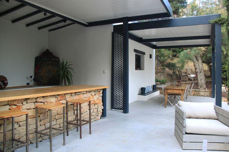 grande terrasse en béton ciré avec espace salon repas bar et barbecue couverte en partie par une pergola bioclimatique