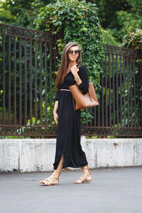 Девушка в длинном черном платье и светлых сандалиях гладиаторах