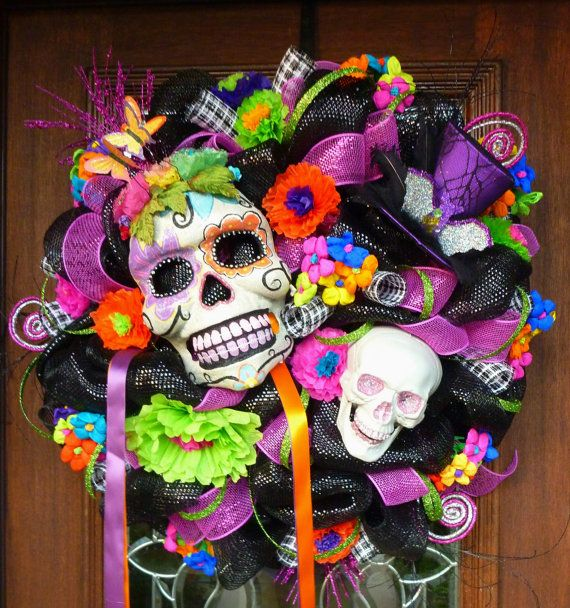 This 26 festive deco mesh wreath features a beautiful DAY OF THE DEAD hand painted mask. It is accented with a purple hat with a sparkly silver bat and