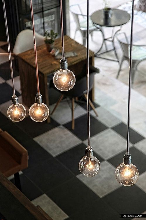 light bulb pendant lights and checkered flooring for certain areas of the studios (e.g. kitchen).