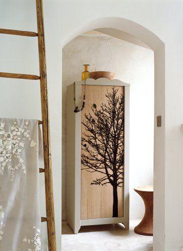 Une étagère transformée en armoire grâce à une planche de bois décorée d'un arbre en pyrogravure