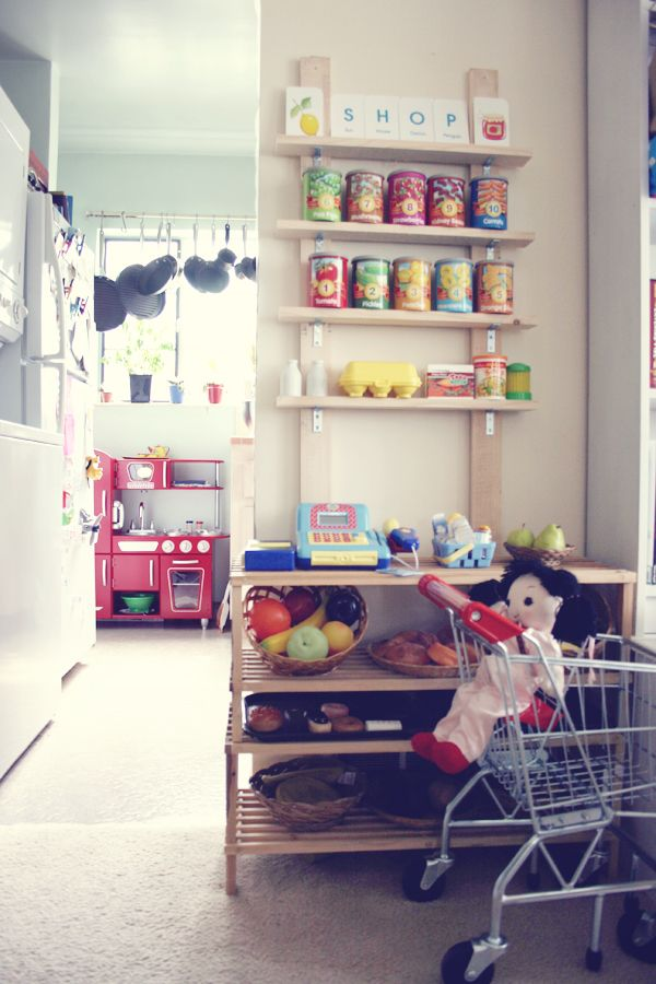 Eva's play kitchen and pretend market with shopping cart. The DIY grocery stand only cost about thirty dollars to make not including the cash register and play food.