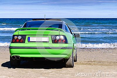 Green sport car on beach sand near sea water. Rear view.