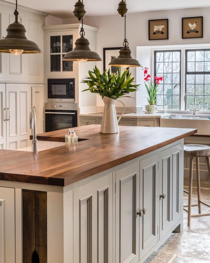 Love the light fixtures & delicate color on the island base with the butcher block.