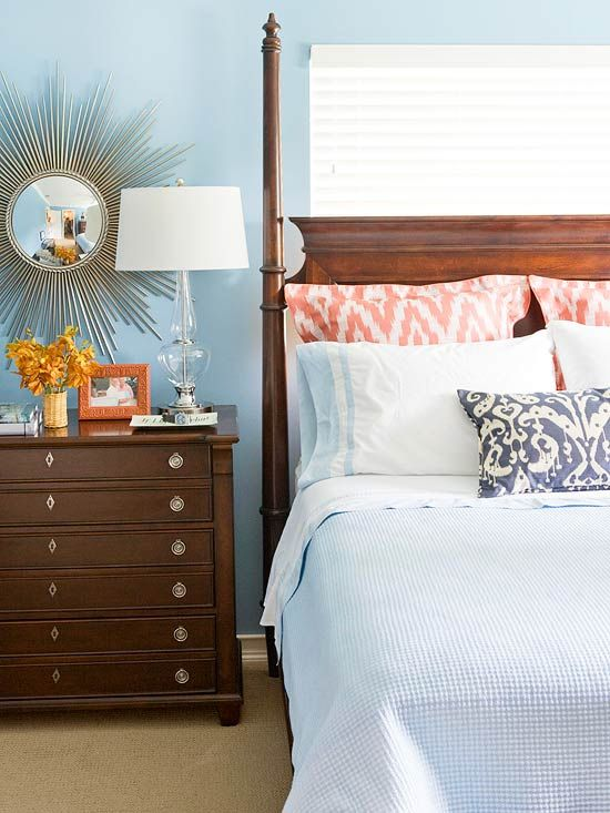 In my own home I love the use of a white or neutral canvas of bed linens with bold patterns and bright pops of color in accent pillows and a quilt laid at the bottom of the bed. The blue walls and dark furniture really mix well together. This room would be a serene getaway for guests.