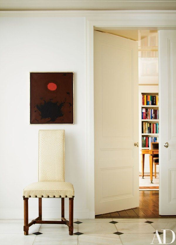 Adolph Gottlieb's painting Looping #2 meets a 1950s Jacques Adnet chair in a New York apartment decorated by Delphine Krakoff of Pamplemousse Design, with interior architecture by Mark Ferguson of Ferguson & Shamamian; the paint color is Benjamin Moore's Marble White.