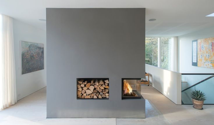 Breaking up the open-plan design, is a 3-sided glass enclosed fireplace, housed in a rectangular form, that also has storage for firewood.