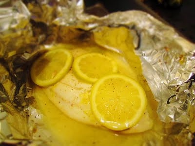 Baked Lemon Tilapia - 1 tilapia filet; 1 lemon, zested, sliced, and juiced; pat of butter; chopped garlic clove; salt; pepper. Preheat oven to 375.  Place tilapia on foil and season with salt and pepper on both sides; add garlic and butter to top.  Zest a lemon over the filet. Thinly slice three slices of lemon from the middle of the lemon so that each slice is uniform in size.  Then squeeze the remaining ends of the lemon over fish. Loosely wrap the fish up in foil. Bake 12-14 mins.