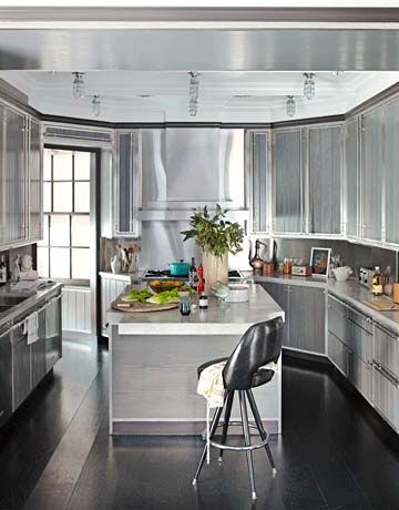 The wall to the right of the cooktop was angled to match the doorway—now this Manhattan kitchen is shaped like a boat, with the cooktop at the prow. A crown ceiling painted white, with Harbor lights from Urban Archaeology, casts a glow over the island. Cutout cners create a friendlier transition to the breakfast area. 1960s barstool from VandM. Sub-Zero 650 refrigerator.