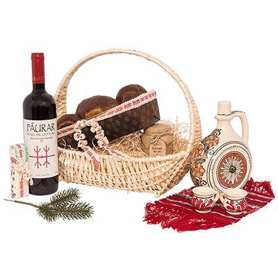 Cadou pentru Craciun AT05 traditional. #Cos #cadou #traditional pentru #Craciun include vin Roșu de Ceptura Făurar 2013 Dealu Mare, #cozonac tradițional, #nougat artizanală, dulceață din #fructe proaspete, ploscă din ceramică pictată, set 2 cescuțe ceramică, #servet traditional. Produsele sunt asezate intr-un coș împletit, decorat cu iarbă naturală de bumbac si fundiță asortată. Cadoul in stil traditional este potrivit pentru a transmite urari de #sarbatori partenerilor sau colaboratorilor.