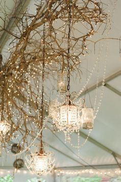Rustic and glamorous. Branch and chandelier hanging wedding decor