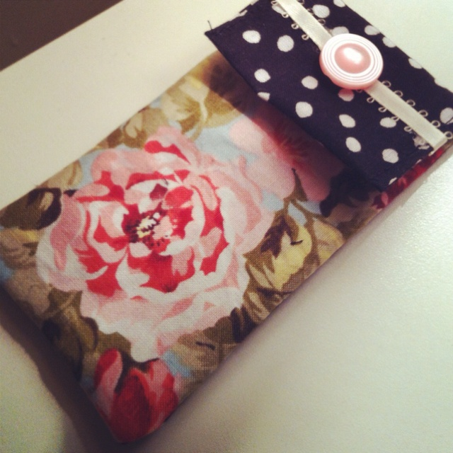 Homemade iPhone case. Machine newer the main case, glue gunned ribbon, hand sewn button, and I used those small Velcro dots for the closure although you could also use the button for the closure. I can't wait to make more of them in different fabrics and decorative accents!
