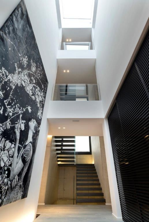 #interbau created a #staircase that connects all of the four floors, placing it in a fair-faced concrete space with embossed resin-coated iron steps, fixed directly to the concrete masonry, and big #railings in monolithic glass. #design #highquality #designforyourhouse #totallycustomized #madeinItaly