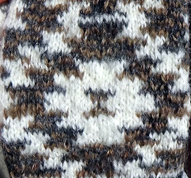 Detail of a Navajo mitten.  There is one main color (white) and two colors that alternate every row (brown and black).