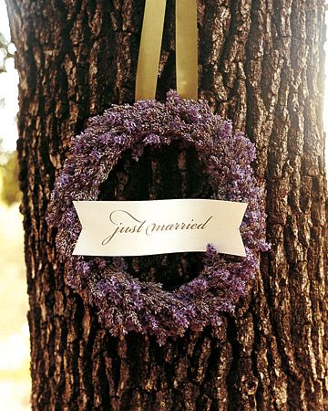 "Fresh stems of lavender are wired to a wreath form; a card-stock sign printed with ""just married"" is tied onto the wreath."