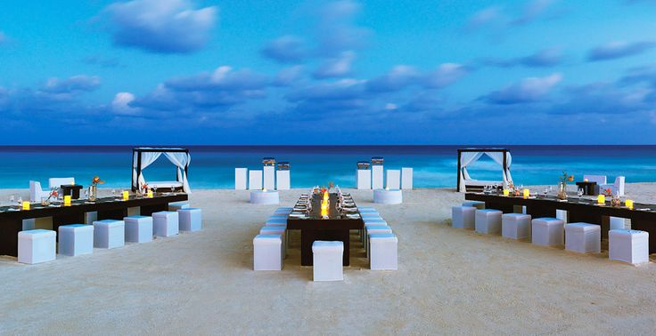 This wedding reception setup on the beach has an intimate campfire ambiance with long tables and fire pits | Le Blanc Spa Resort in Cancun, Mexico