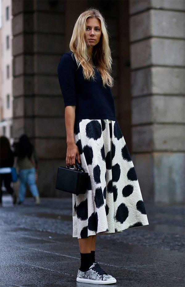 Street style look com saia midi estampada, blusa preta, tênis brilhante e meia aparente.