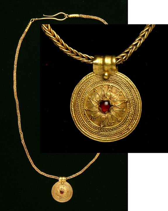 Greece. Hellenistic Gold Necklace with Pendant.Circa late 4th-3rd Centuries B.C. A loop-in-loop chain beautifully displays the disk pendant with a cabochon garnet centrally set within a shield-like convexity. A similar necklace can be found and described inCatalogue of the Jewellery, Greek, Etuscan, and Roman, in the Departments of Antiquities, British Museum, by Marshall, #2062. 18 1/4 in. (46.4 cm. in length). Weight: 15.1 grams.