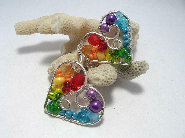 Srdcové duhovky - náušnice Kolekce Rainbow - veselá , hravá, okamžitě upoutá:-) Tvar: srdce Materiál : měděný postříbřený drát, rokajl, broušené korálky, voskové korálky Použité komponenty: bižuterní v barvě stříbra, afroháček, PVC puzeta Rozměry: délka: 2 cm šířka: 2,5 cm