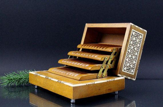 Willkommen im Shop GermanVintage4You.  Wunderschöne Zigaretten Box aus Holz mit Mosaik Muster.  Die Box bietet platz für 40 Stück Zigaretten.  Die Box ist für Zigaretten ohne Filter oder kurze dünne Zigarren. Es passen Zigaretten von einer länge: 7,5 cm ( 2.95 inches ) in die Box hinein.  Größe der Box  Höhe: 9,5 cm ( 3.74 inches ) Länge: 17 cm ( 6.69 inches ) Breite: 13 cm ( 5.11 inches ) Gewicht: 791 Gramm  Der Zustand der Box ist sehr gut. Versand: Ich verwende zum Verpacken hochwertiges…