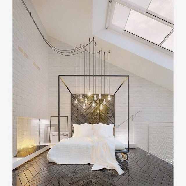 minimalist bedroom in brick loft with chevron floors and Edison bulb chandelier