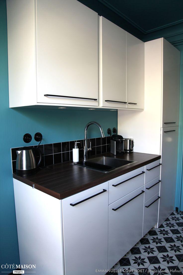 Une cuisine blanche et bleu, dans laquelle des carreaux de ciments habillent de sol.