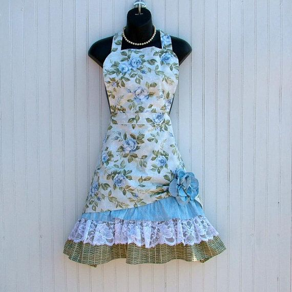 This is my Petticoat Ruffle Apron which has been featured on FOOD NETWORKS Cake Wars. With its ruffles it is so fun to wear. The Blue Rose floral print is a heavier cotton for long wear and looks like a retro print. The pull-up with the flower shows off the rows of lace and fabric ruffles and adds to that special look. The flower is safety pinned on to a reinforced area on apron for easy removal for laundering. . The neck ties in the back for comfort and easy fit. The fabric waist ties (not…