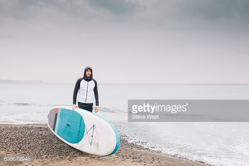 Athletic young man standing on the beach next to a Stand Up Paddleboard .