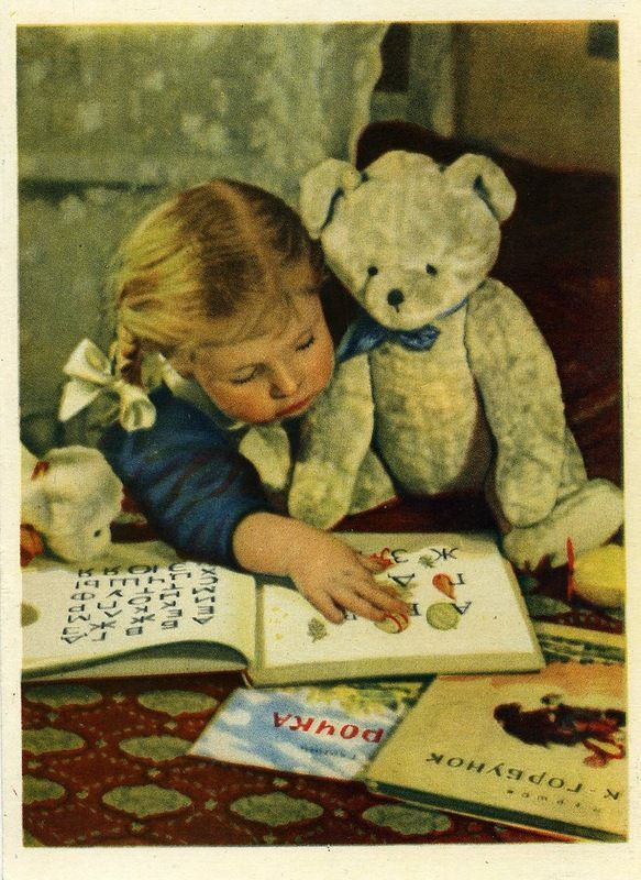 Little Girl Reading with her Teddy Bear (looks like Russian)!