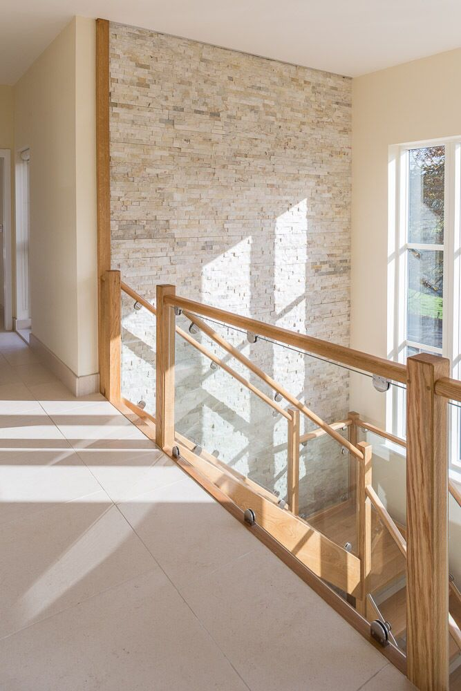 Beautiful hallway, stairs and landing. Cream quartzite splitface tiled feature wall from Mandarin Stone along with Moleanos honed limestone tiles on the floor. www.mandarinstone.com