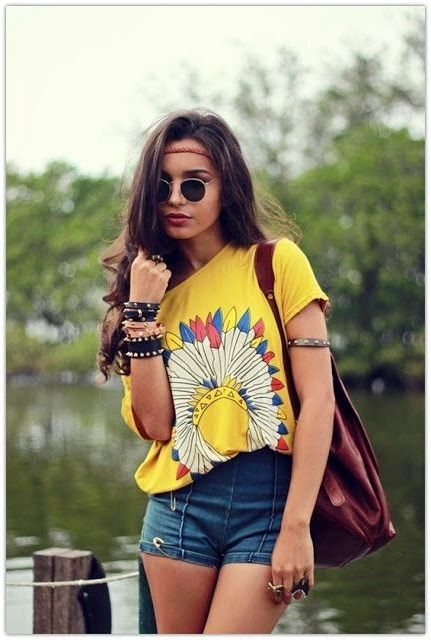 Девушка хиппи в обтягивающих шортах, футболке с принтом и браслетами на руке