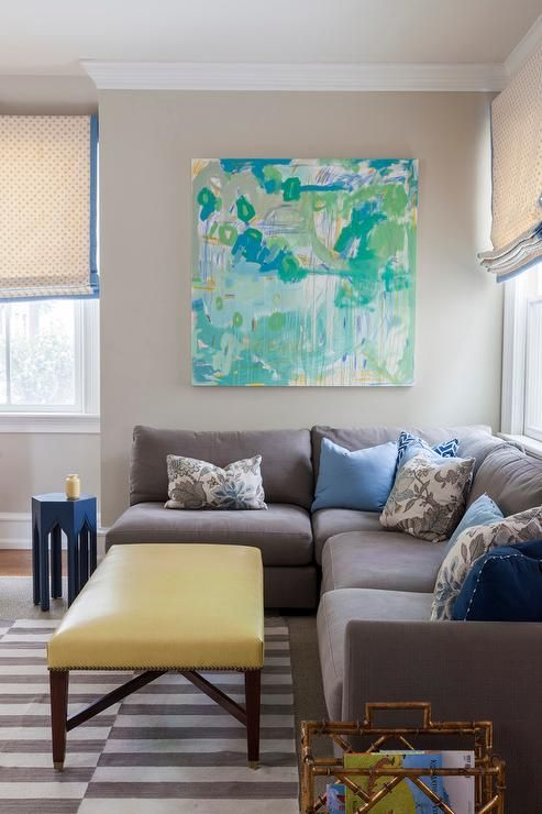 Contemporary living room boasts a turquoise and green abstract art piece over a gray armless sectional adorned with blue pillows flanked by a blue Moroccan accent table to the left and a gold bamboo magazine holder to the right facing a yellow ottoman doubling as coffee table atop a gray striped rug.