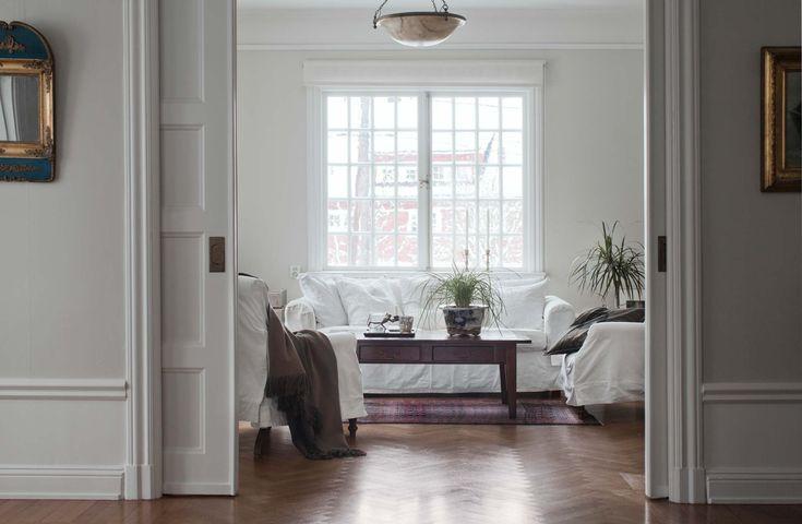 Vardagsrum och tv-rum ligger i fil med skjutdörrar emellan. Vita fåtöljer från Spanien, soffa, Zandvoort och bord Newport. Alabasterlampan med små lejonmaskaroner är ett auktionsfynd.