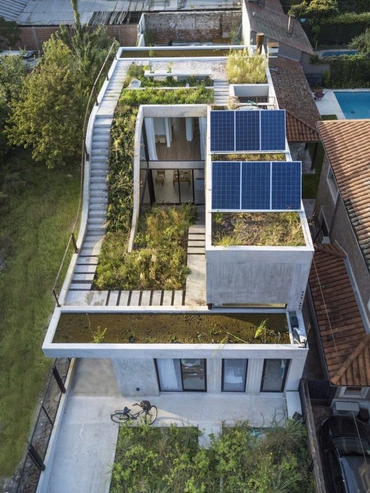 Solar panels are installed on the roof of the house, suggesting a sustainable design approach