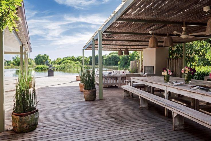 Gran deck de madera con pérgola uniendo una casa de fin de semana con una laguna en Pilar.