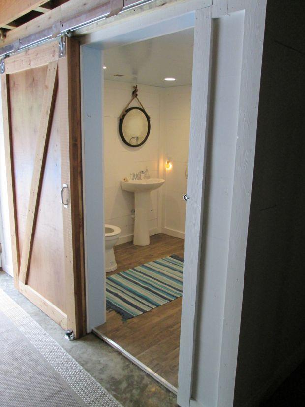 Beach style bathroom in basement with barn style sliding for Basement sliding doors