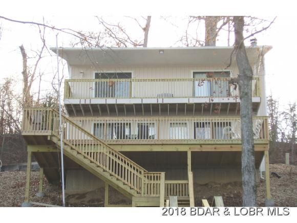 Awesome Main Channel Lake View!! Open Living/Kitchen/Dining with a Natural Stone Wood Burning Fireplace. The Kitchen has lots of Cabinets and Breakfast Bar and the Dining Area has Wood Decor accents. Master Bedroom/Bath has Walk-In Shower and private Decks off both the Lake Front Bedrooms. There is new Decking with a beautiful Lake View and a 2nd Tier Lot included. The concrete 2-Well Dock has 2 Boat Lifts. Great location by Land or Water in Camdenton MO