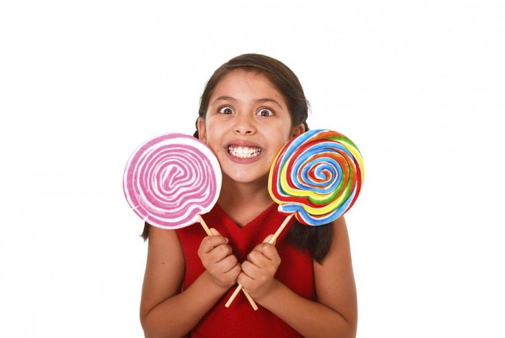 happy female child holding two big lollipop in crazy funny face expression in sugar addiction