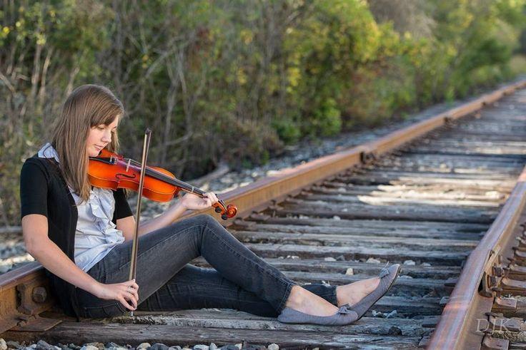 Adorable violin photography on railroad tracks!