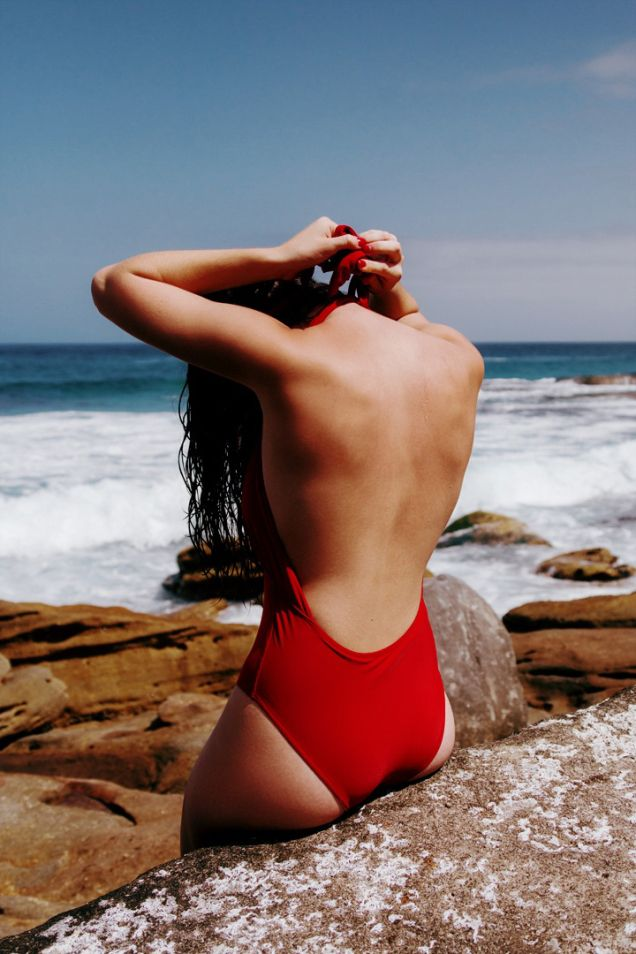 Soaking up some rays in a hot red swimsuit.