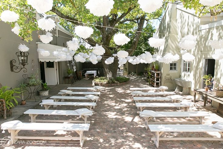 Outdoor ceremony at Cafe Felix under the trees with white benches and tissue paper pom pom.