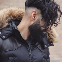 Franja alongada também é uma opção para os meninos de cabelo ondulado ou cacheado. Long curly fringe undercut hairstyle for men